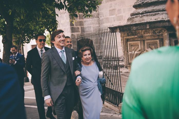 El novio feliz del brazo de su madre llegando a la iglesia para su boda