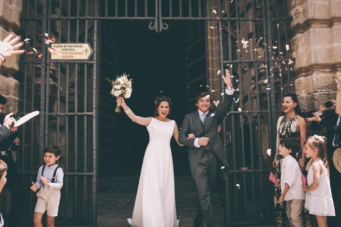 Los novios salen de la iglesia entre petalos y alegria
