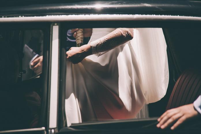 Las manos de la pareja en el coche de novios