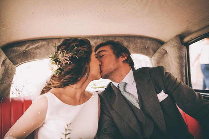 Los recien casados se besan camino al banquete